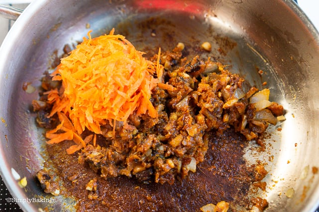 adding grated carrots to the mushroom and spices with miso paste