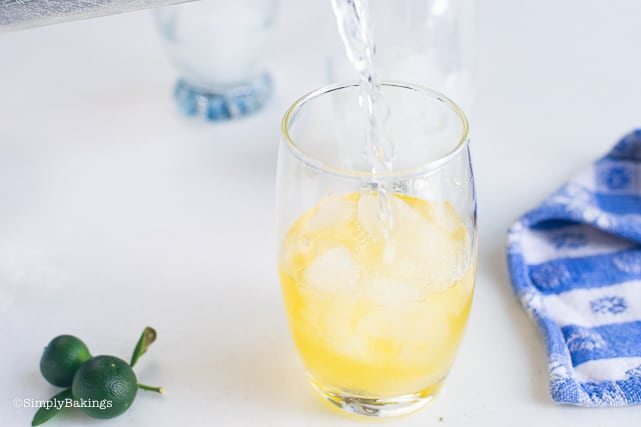 adding water to the glass of calamansi juice