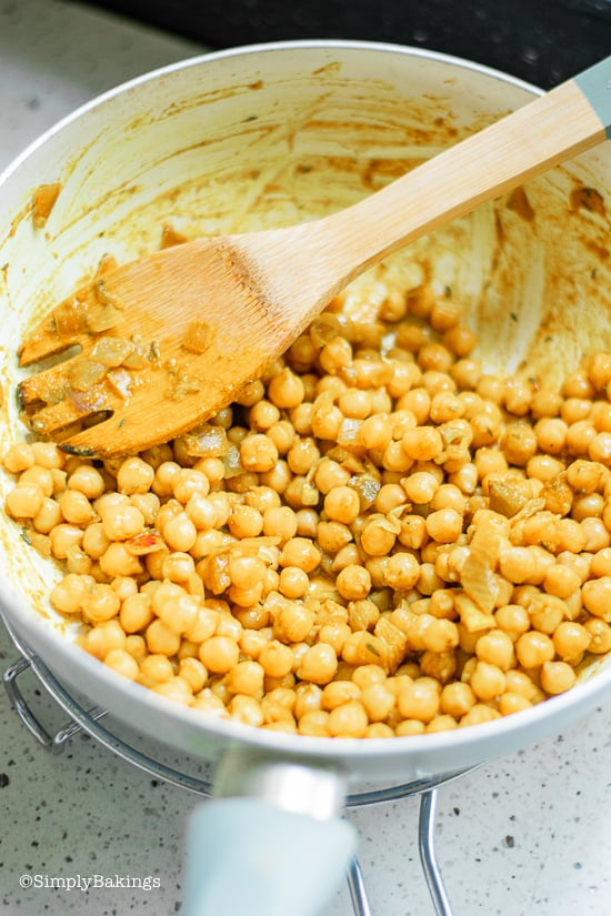 mixing chickpeas to the curry paste to make curried chickpea wraps
