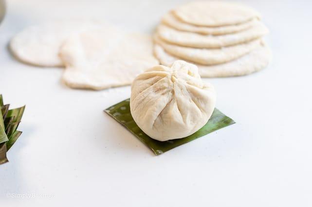 ready to steam siopao bun on top of a banana leaf