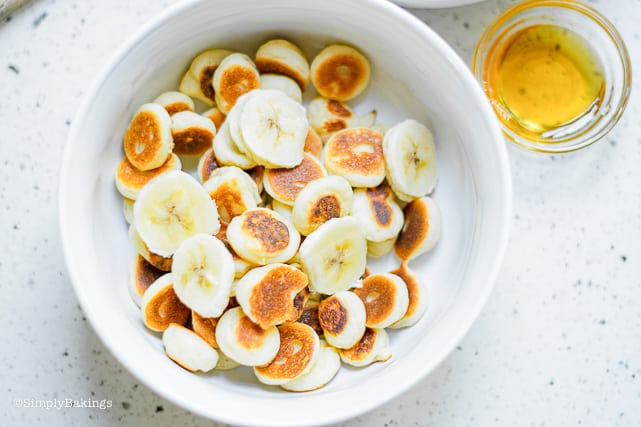 a bowl of TikTok pancake cereal with sliced bananas and agave nectar on the side
