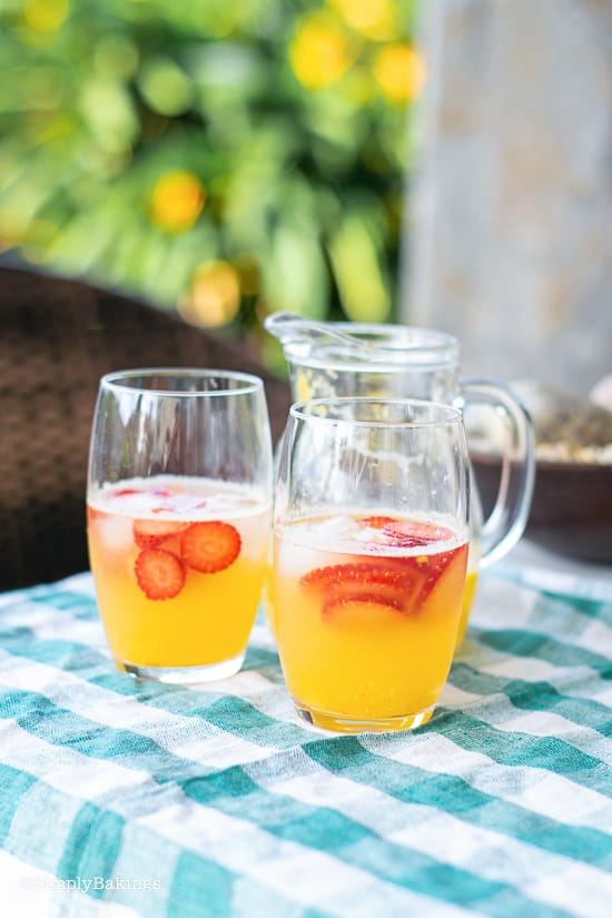 refreshing strawberry mango lemonade in a glass and pitcher