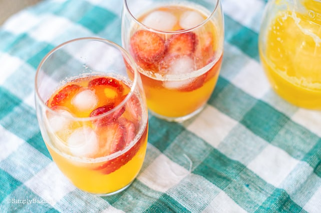 two glasses of strawberry mango lemonade with ice cubes