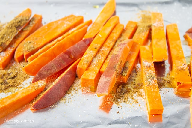 seasoned sliced sweet potatoes for vegan collard wraps ready to be roasted