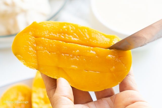 slicing the fresh mango to be used in the Filipino Mango Ice Cream