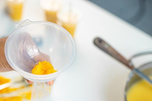 adding fresh mango into the plastic wrap to make Vegan Mango Ice Candy