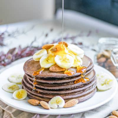 agave syrup being poured on vegan chocolate pancakes