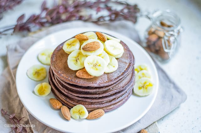 vegan chocolate pancakes topped with bananas and almonds on a white plate