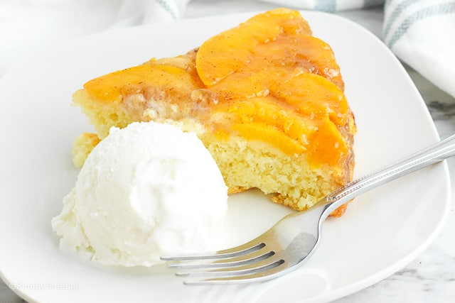 one slice of a Peach Upside Down Cake and a dollop of ice cream