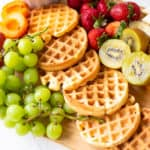 waffles, fruits, on a brown cutting board