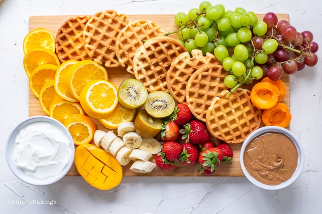 waffles and fruits on a cutting board with yogurt and almond butter