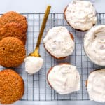 pumpkin whoopie pies on a cookie sheet with pecan cream cheese frosting