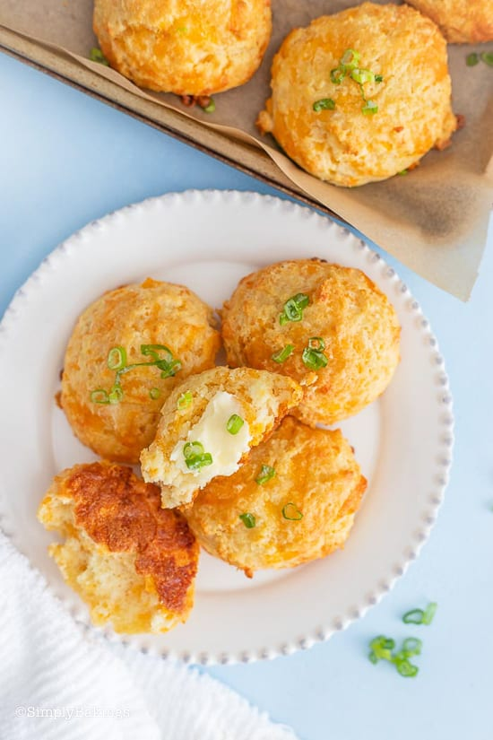 baked biscuits on a white plate and pan garnished with scallions