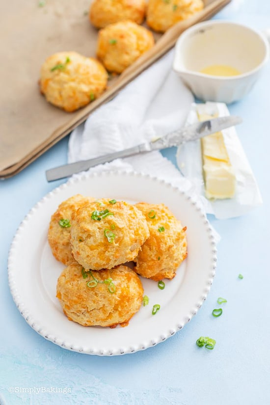 biscuits on a white plate with butter on the side and a pan of biscuits