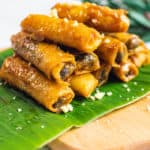 sweet potato spring rolls with a banana leaf on a wooden board