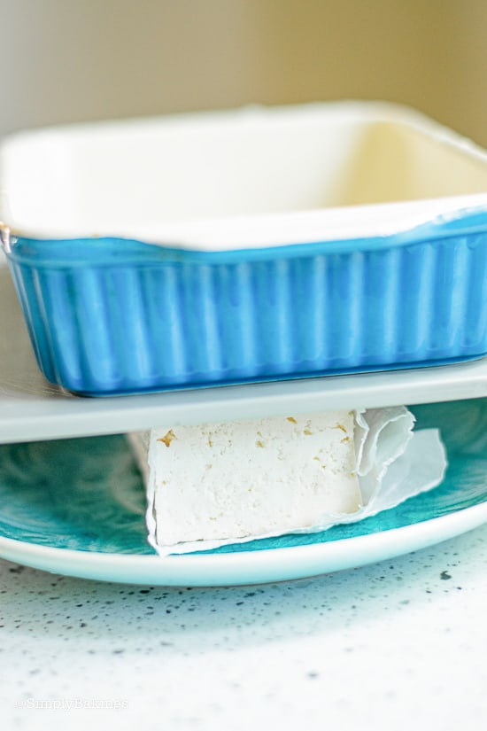 removing water from the tofu by placing heavy objects on top of tofu