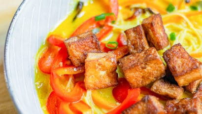 vegan thai curry noodle soup in bowl garnished with fried tofu and red bell pepper