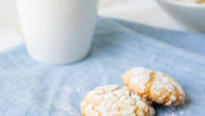 3 cookies on a blue cloth with a cup of coffee