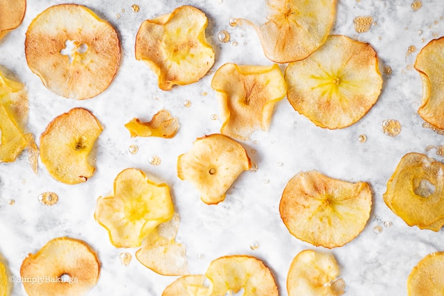 Baked cinnamon apple chips on parchment paper