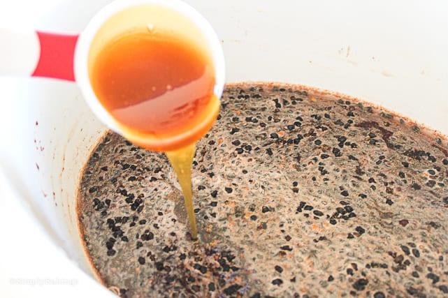 Adding raw honey to a bowl of elderberry syrup