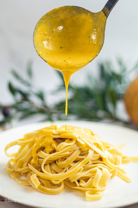 pouring the sauce over fettuccine pasta