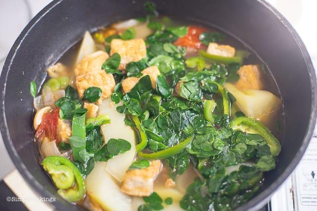 Tinolang Manok cooking in a black wok