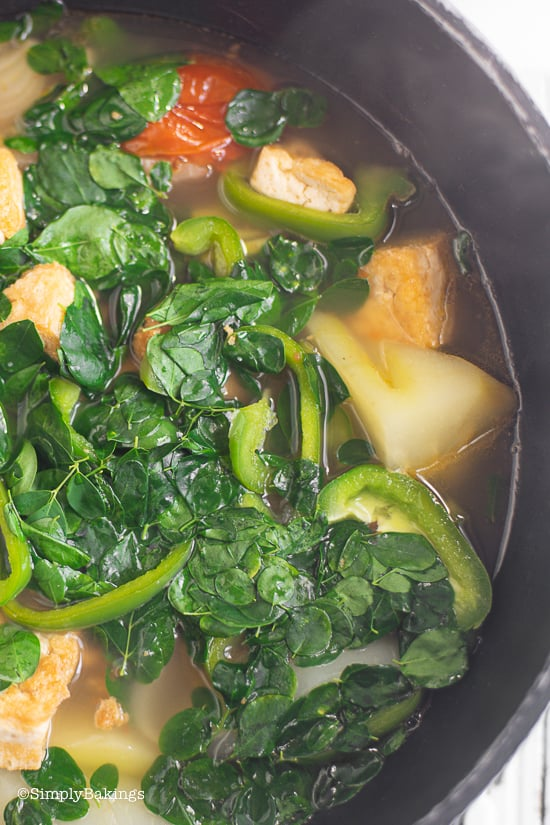 Filipino Tinola Soup with cooked malunggay leaves and green peppers