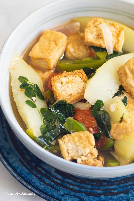 vegan tinola in a white bowl with mulunggay, green papayas, and tofu