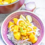 Potato and Chickpea Curry over white rice in a pink bowl