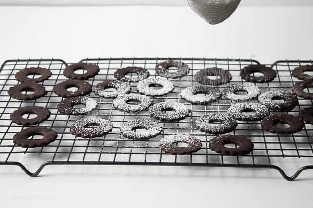 sprinkling powdered sugar on chocolate cookies on a cookie rack