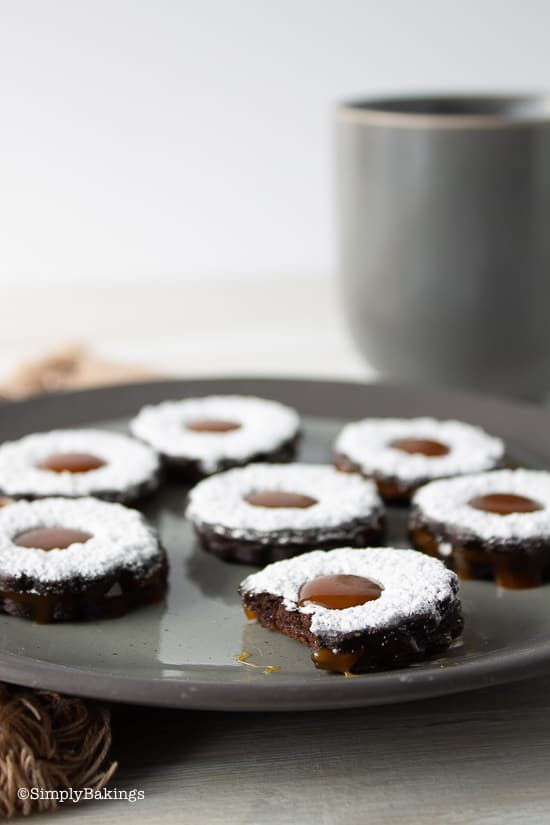 Caramel filled chocolate cookies on a gray plate with a cup of coffee