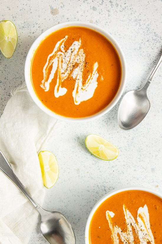 two bowls of cream of tomato soup with a stainless spoon beside each bowl