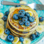 egg free pancakes topped with fresh blueberries, banana slices and honey on a sky blue plate with a stainless spoon