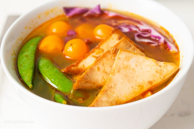 lemongrass soup loaded with some fried tofu, tomatoes, red cabbage and snap peas