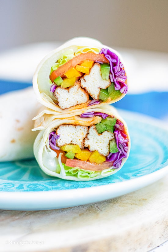a tofu wrap cut in half and placed on a sky blue plate