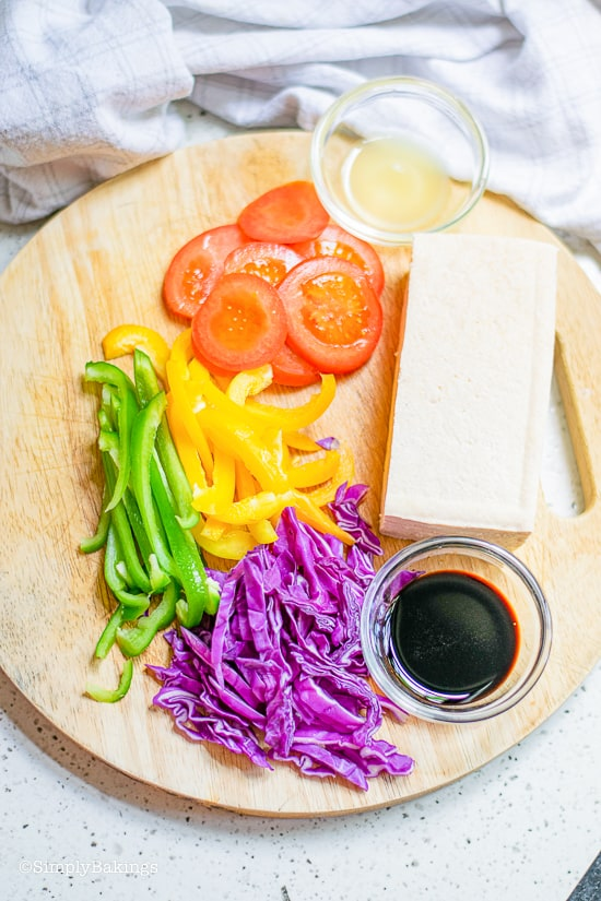 ingredients for tofu wraps on a circular wooden board