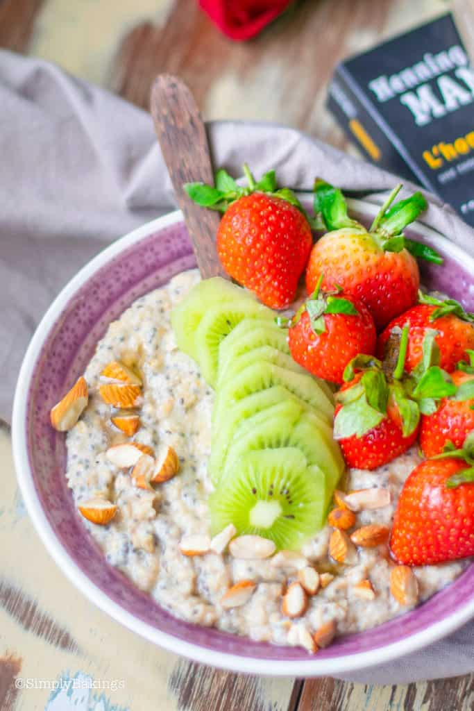 a bowl of spicy chia oatmeal topped with kiwi, strawberry and chopped almonds