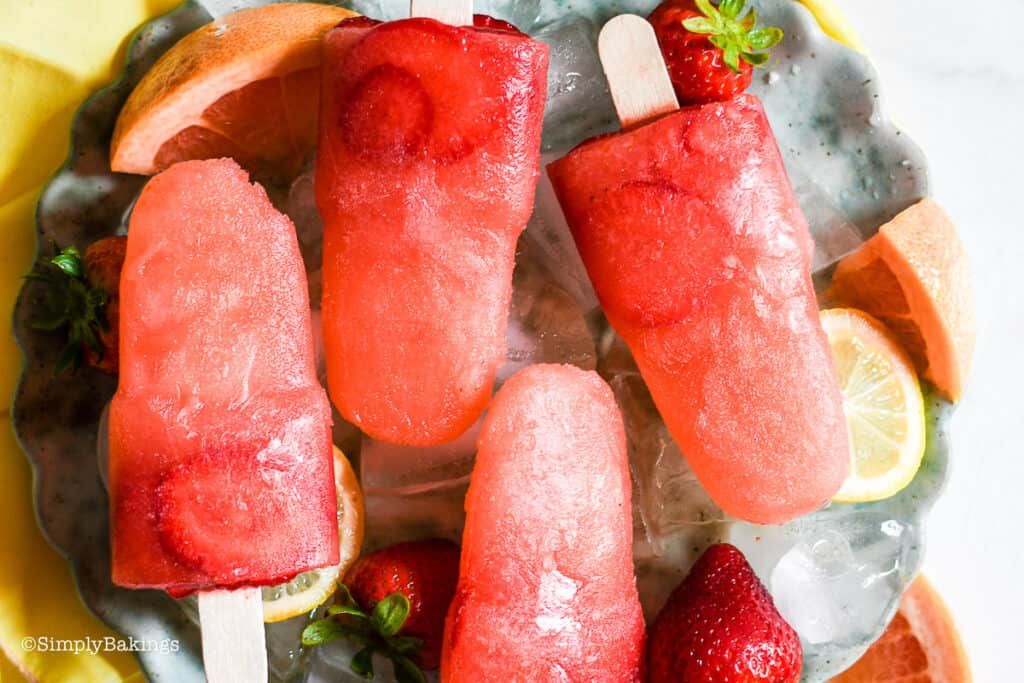 grapefruit strawberry popsicles on a round plate with ice, strawberries, cliced lemon and grapefruit