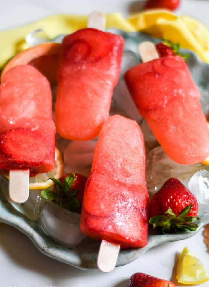 Grapefruit Strawberry Popsicles with ice and fresh strawberries on a round plate