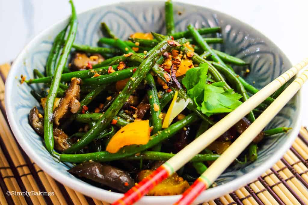Green Beans with Black Bean Sauce in a blue bowl with chopsticks