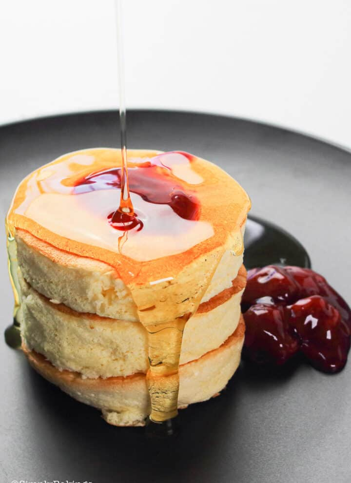 fluffy Japanese panckes on a black plate with sweet berry sauce