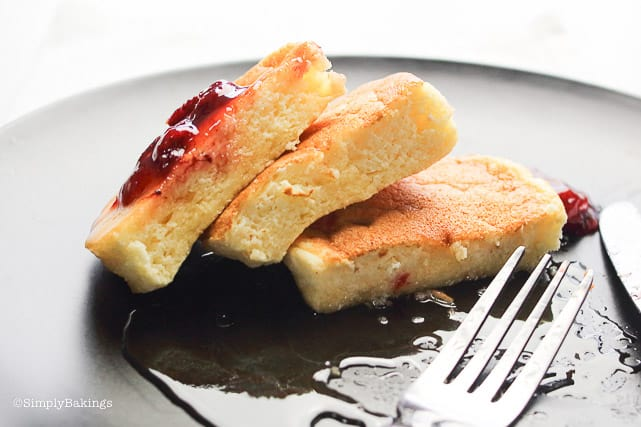 slices of Japanese pancakes on a black plate with a fork and berry sauce