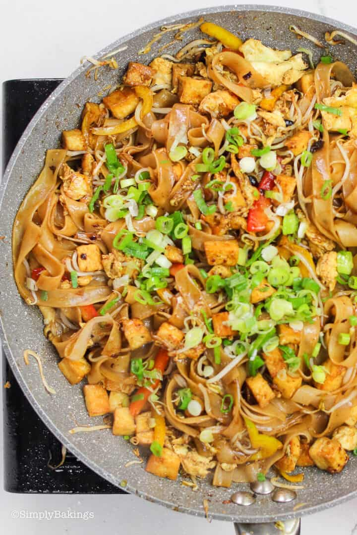 Malaysian Stir Fried Noodles in a large pan and garnished with green onions