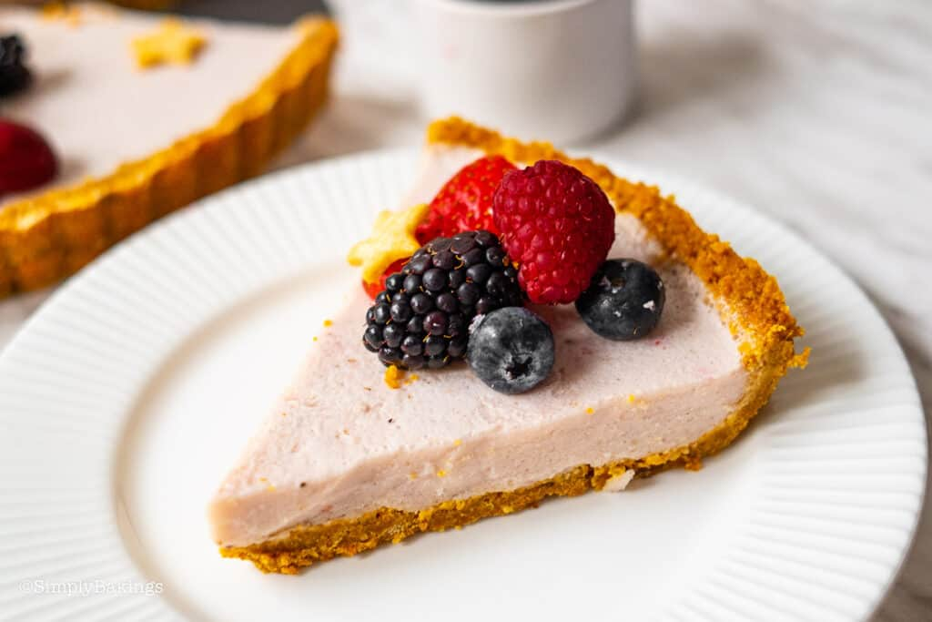 a slice of berry fruit tart topped with mixed berries on a white plate