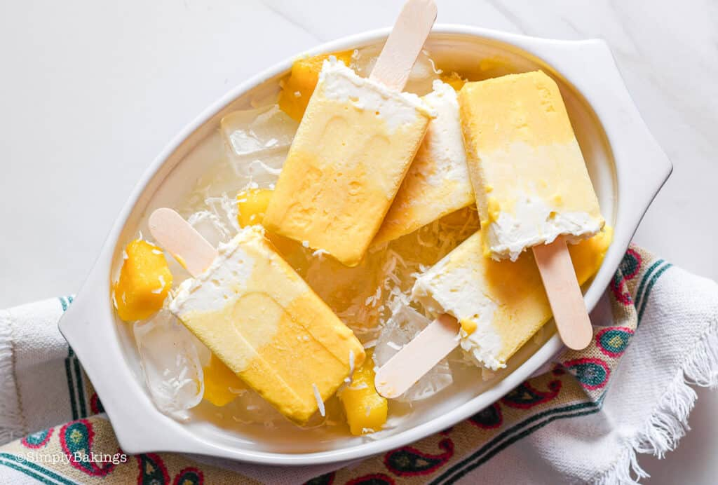 Piña Colada Mango Popsicles with some ice cubes in a white bowl