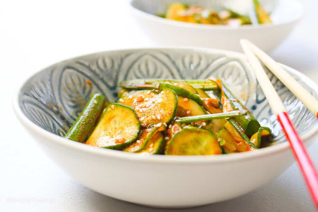 Asian cucumber salad in a bowl with chopsticks