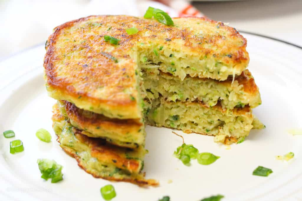 a stack of sliced Zucchini Pancakes on a white plate and garnished with green onions