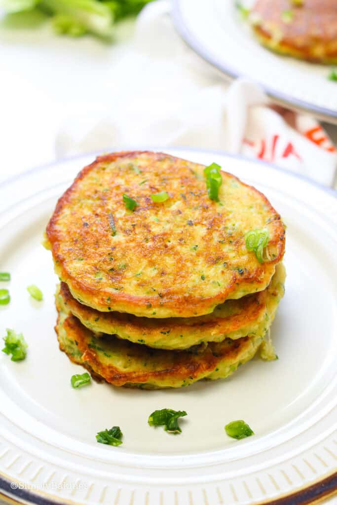 Zucchini Pancakes on a white plate and garnished with green onions