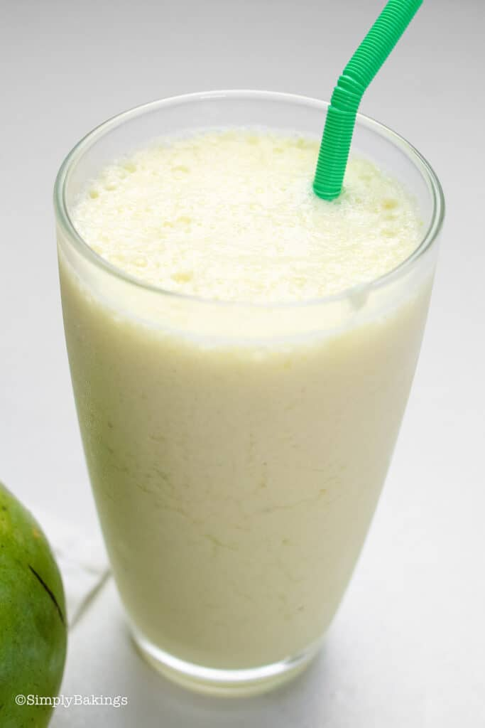 green mango shake in a tall glass with a green straw