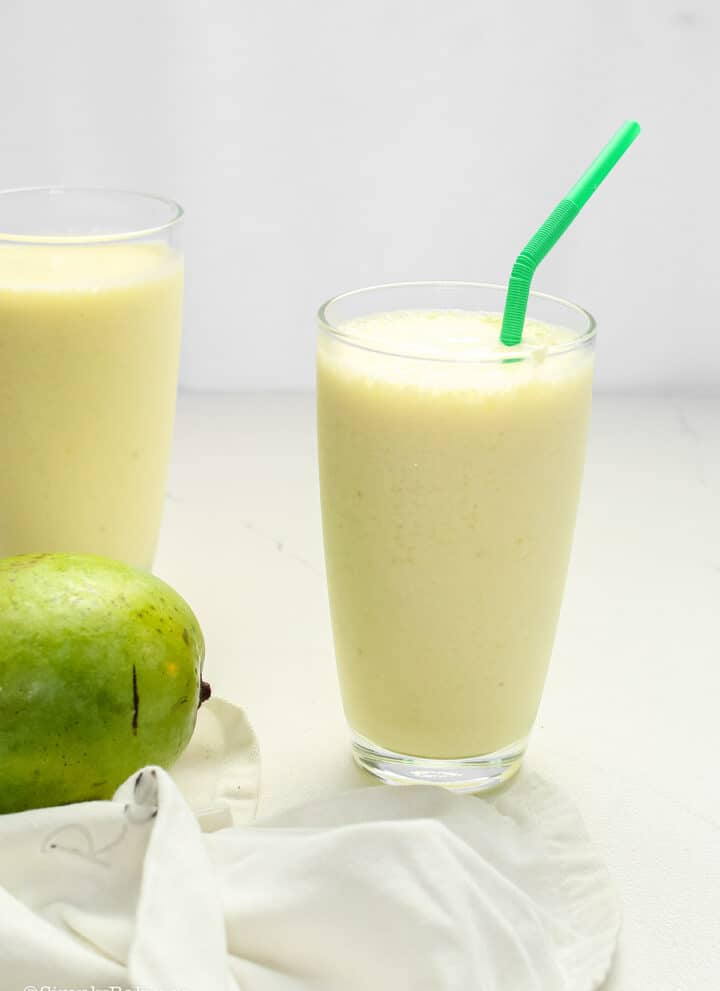 delicious green mango shake in a tall glass with a green straw